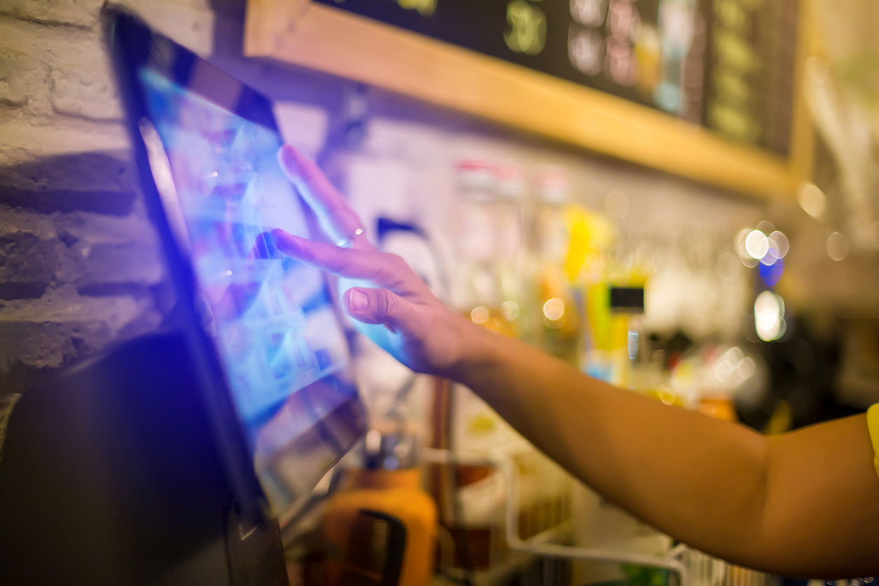 Blurry picture of cashier is making order on touch screen of computer in cafe or store.