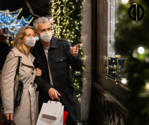 A couple wearing masks admiring a store's holiday display