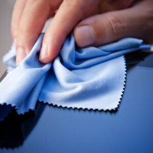 Hand cleaning a tablet PC with a cloth. Shallow depth of field.