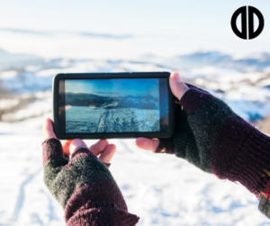 Woman taking a photo of a snowing mountain on her phone during winter